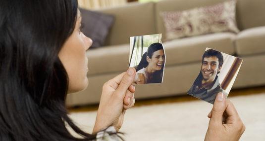 Chica rompiendo una foto tras romper con su pareja